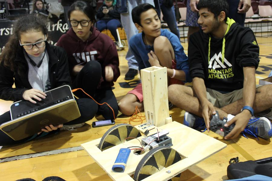 Building team members Alida Kaufmann, Anne Li, Akshat Shah, and Dhruv Modi discuss future modifications to their robot.