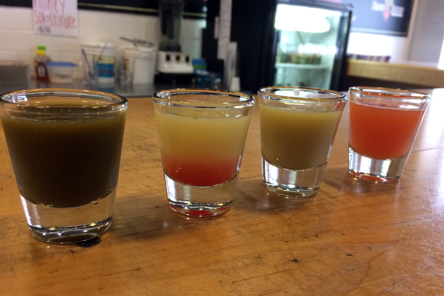 """Another way to get a healthy boost of energy is in the form of Wellness Shots, available at Roots Pressed Juices. These shots are a series of small, concentrated juices that are consumed one after the other. In this series, dandelion, lemon with B12 vitamin added, and ginger are followed by a """"chaser"""" of Bee Well juice."""