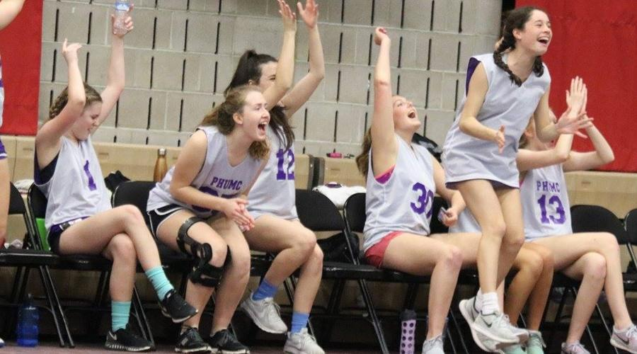 Team members of the Kittens celebrate their lead after a three point shot, showing the joy that comes with every church league basketball game.