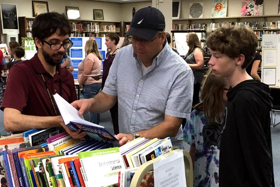 Teachers discuss science fair topics with parents and students.