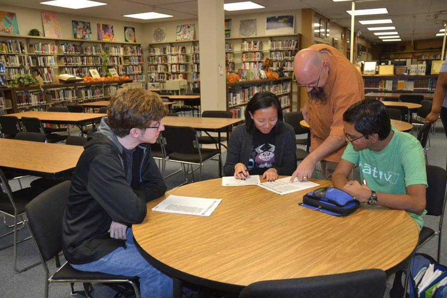 Juniors Jackson Pierce (left), Analise Presley (center), and Nimesh Wijewardane (far right) prepare for the PSAT with the help of English teacher Jacob Morris in the library on the morning of Oct. 12.