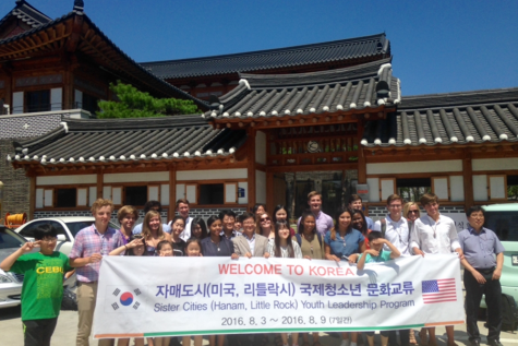 Students and chaperones pose in front of a traditional Korean restaurant.