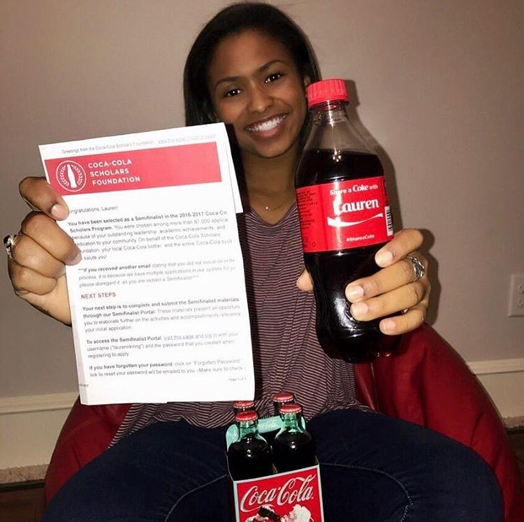 Senior Lauren King smiles big with her custom Coca Cola and letter advancing her to the semi-finals of the Coca Cola Foundation Scholarship.