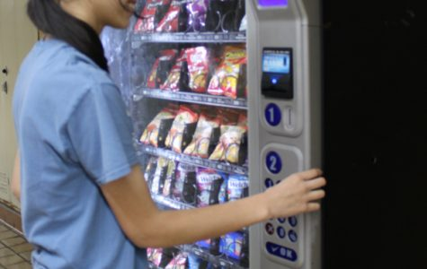 Senior Evalyn Berleant tries out a vending machine for a mid-day snack.