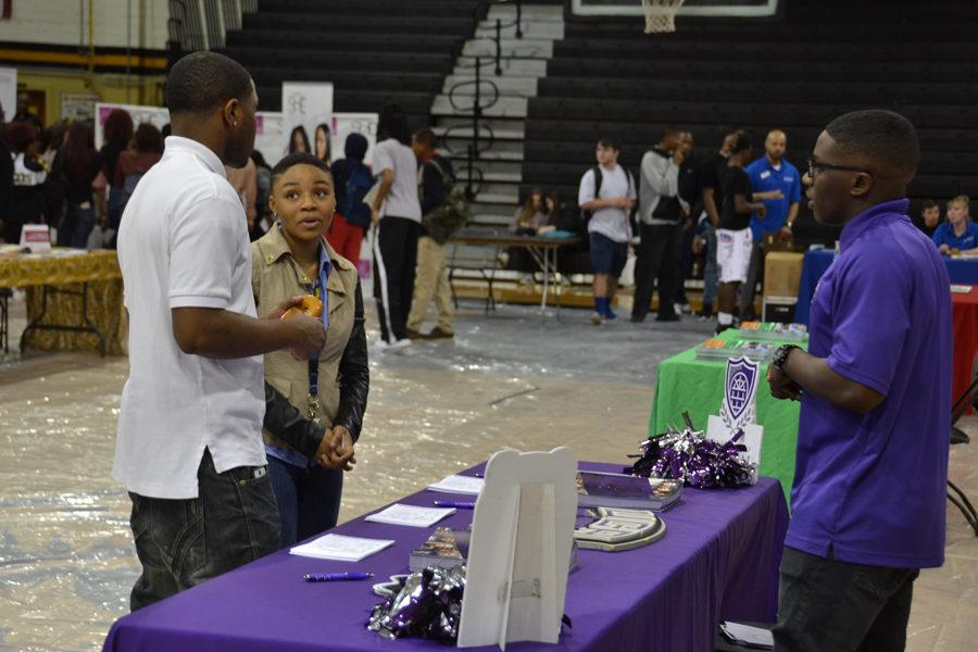 Seniors Terryl Humphrey and Daiuna Shields converse with a recruiter from the University of Central Arkansas.