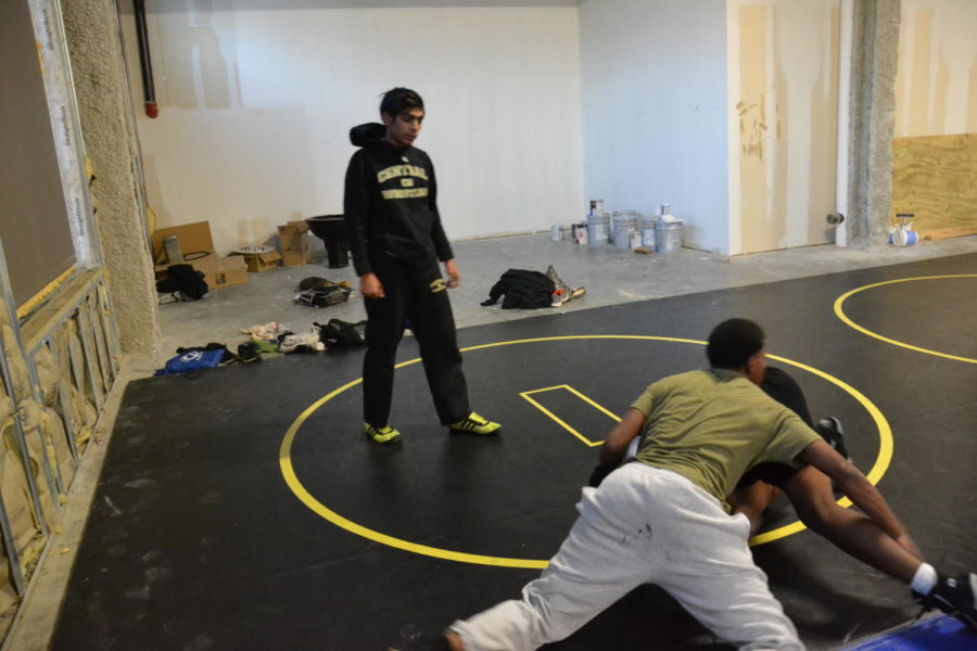 Senior Faraz Sayyed coaches two of his teammates as they warm up for their match on December 9th. Central went on to win 1st in the tournament