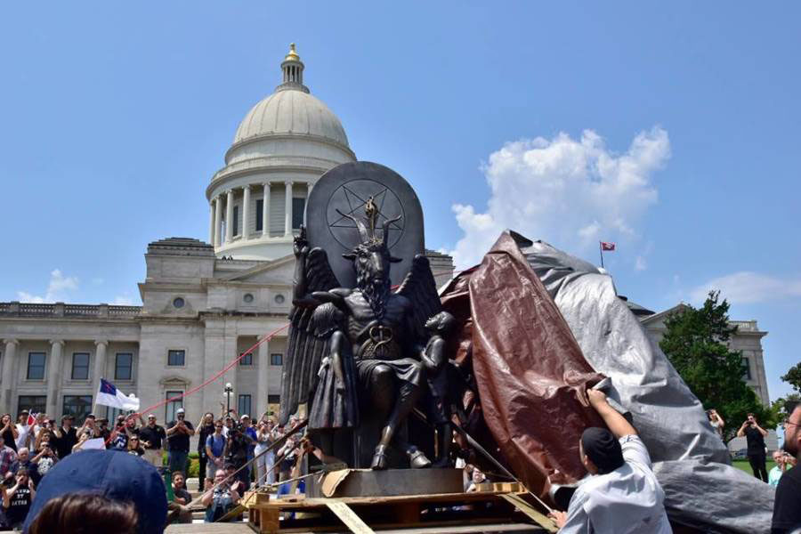 """Satanic Temple members unveil their statue in protest for religious freedom. """"This is not a protest against the Ten Commandments. This is a rally for reason in the face of prejudice, progress in the face of decline, liberty in the face of rising theocracy, and toleration in the face of infantile tribalisms,"""" Satanic Temple spokesman Lucien Greaves said. (photo from the Arkansas Times)"""