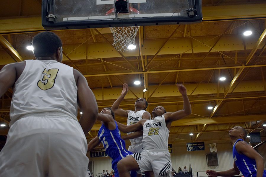Sophomore Ubong Etin and senior Rajhon McIntosh climb the back of a Bryant Hornet to grab a rebound during a heartbreaking 45-49 loss. (photo by Mollygrace Harrell)