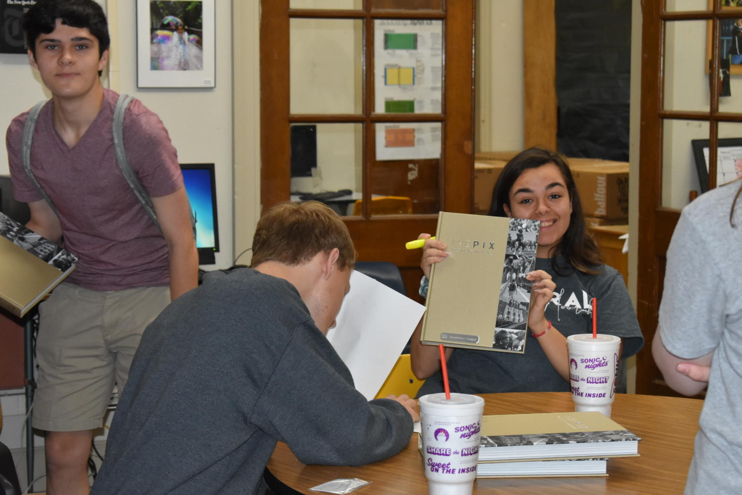 Hannah Berry helps distribute the 2018-2019 yearbook while other staffers, Carson Whaley and Alex Buller mark off names of those who already picked up their yearbook.