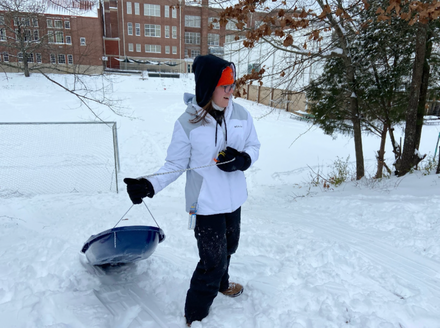 """Senior Madeleine Gess makes her way up the hill at Pulaski Heights Middle School. Gess and her friends spent the afternoon sledding and exploring the snowy campus. There was an extra nostalgia factor as the group walked the grounds of their old school. """"For PH, it's always fun to go back and see how things are and how they've changed. Being on the playground brings back so many memories of all the crazy things we used to do during recess every day,"""" Gess said. """"I do find it kind of sad right now though, seeing all of the gates surrounding different playgrounds because of the pandemic."""""""