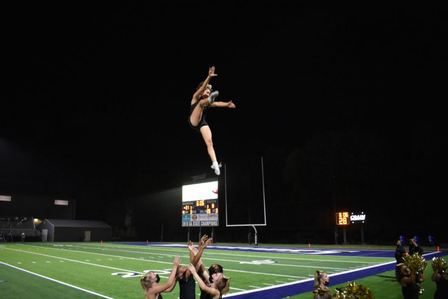 Junior flyer, Malia Clyburn, explodes into a hitch-kick basket toss with the help of her bases Ella Feuers, William Smith, Camryn Barnett, and Samia Smith.